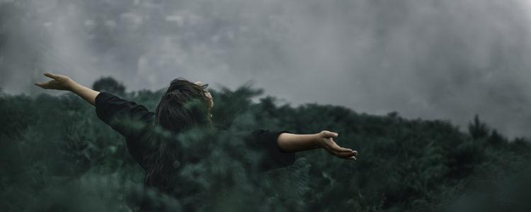 Dívka stojí v dešti s rozpaženými pažemi