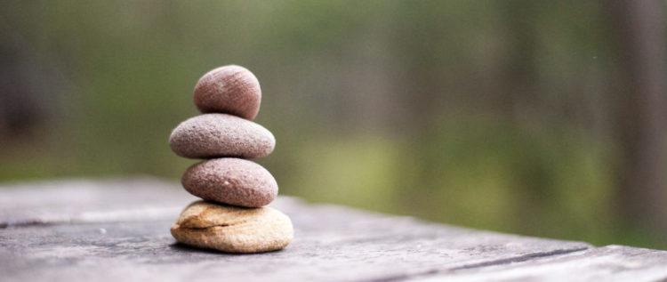 Čtyři kamínky tvoří sloupec na dřevěném stole