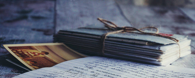 Dopisní obálky svázané režným provázkem, fotografie, dopis