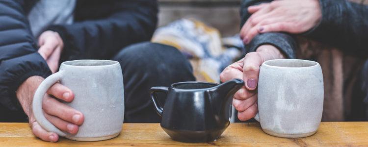 Muž a žena drží dva velké šedé hrnky s čajem a povídají si