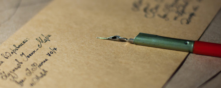 Kovové pero leží na obálce s nadepsanou adresou