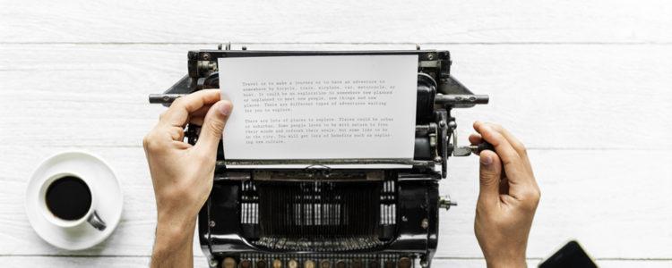 Pohled shora na mužské ruce upravující papír s textem na starém psacím stroji