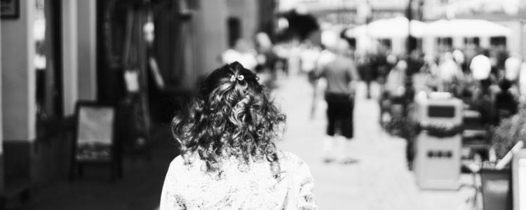 Kudrnatá dívka na rušné letní ulici, zezadu, černobílá fotografie